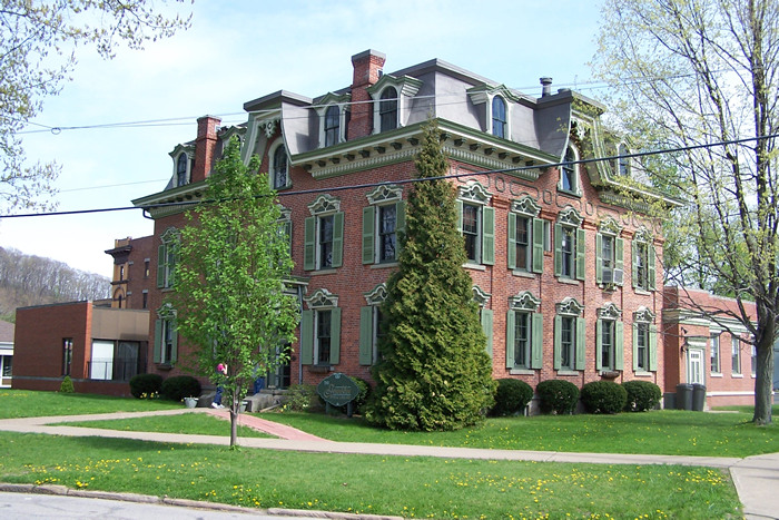 Red brick Victorian mansion three stories with multiple chimneys and green shutters